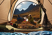 View from inside a tent looking out at hikers and the Arrigetch creek valley, Xanadu (left) Arial and Caliban mountains, Brooks range, Gates of the Arctic National Park, Alaska.