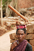 'A woman day labourer carries a digging tool on her head as she returns home; Kharigoda Village, Giajapati District, Orissa, India'