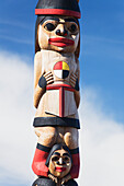 'Human figures carved and painted on a wooden totem pole against a blue sky; Whitehorse, Yukon, Canada'
