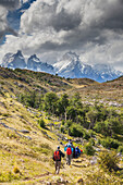 'Hikers walk along a trail in the Torres del Paine National Park; Patagonia, Chile'