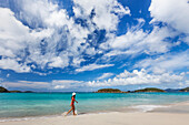 'Lady walks along the tropical beach in the Virgin Islands; United States of America'