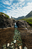 'Man looking at small waterfall near the Fairy Pools in Coire na Creiche, Black Cuillin; Isle of Skye, Scotland'