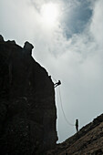 'Silhouette of people abseilling off the Inaccessible Pinnacle at the summit of Sgurr Dearg; Isle of Skye, Scotland'