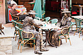 'Stand-still artists dressed as old fashioned mountain climbers having a coffee break in centre of Chamonix-Mont Blanc; Chamonix, Mont Blanc Valley, France'