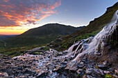 Scenic sunset view of a waterfall at Summit Lake State Recreation Site, Hatcher Pass, Southcentral Alaska, Summer