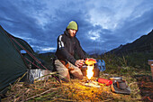 Swiss biologist and photographer warms hands while lighting camp stove along Kukak Bay at dusk, Katmai National Park, Southwest Alaska