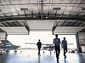 'Three businessmen entering airplane hangar; Langley, British Columbia, Canada'