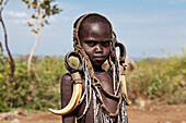 'Portrait of a child decorated with tribal accessories; Omo Valley, Ethiopia'