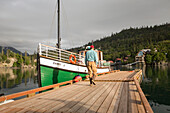 Tourist walking towards the Kachemak Bay Ferry vessel, the Danny J, at Halibut Cove, Southcentral Alaska