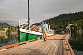 Tourist walking towards the Kachemak Bay Ferry vessel, the Danny J, at Halibut Cove, Southcentral Alaska