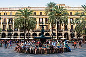 'People sitting on the edge of a water fountain at Plaza Real; Barcelona, Catalonia, Spain'