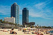 'A crowded Barceloneta beach with skyscrapers in the distance; Barcelona, Catalonia, Spain'