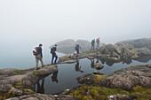 'Hikers walking past small loch in the mist below Sgurr Alasdair in the Black Cuillins; Isle of Skye, Scotland'