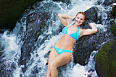'A young woman wearing a bikini and standing in a waterfall; Hawaii, United States of America'