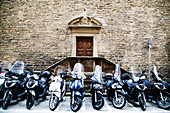 'Motorcycles parked in a row outside the entrance to a stone building; Florence, Tuscany, Italy'