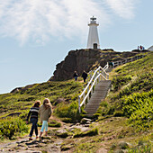 'Tourists walking to steps leading up to a lighthouse on Cape Spear; St. John's, Newfoundland and Labrador, Canada'