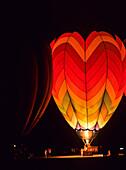'A hot air balloon illuminated at nighttime; Tahlequah, Oklahoma, United States of America'