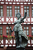 'Close up of bronze female statue with sword and scale against tudor style buildings in the background; Frankfurt am Main, Germany'