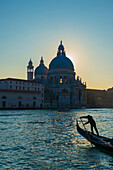 'Gondolier paddles his gondola with buildings and a church along the shoreline at sunset; Venice, Veneto, Italy'
