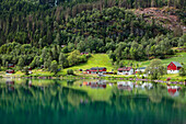 'The tranquil water of Nordfjorden reflecting the trees, houses and barn; Olden, Norway'