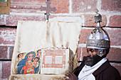 'Priest with crown and holy book, Nakuta Laab monastery, near Lalibela; Amhara region, Ethiopia'