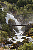 'Tourists stand on a bridge over a river in the mist of a waterfall; Olden, Norway'