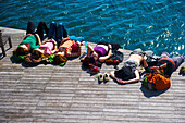 'A group of people laying on a wooden dock at the water's edge in the warm sunshine; Barcelona, Spain'