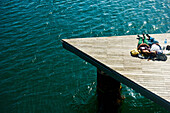 'A couple laying on a wooden dock at the water's edge in the warm sunshine; Barcelona, Spain'