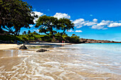 'Lady in red walks along Kauna'oa Beach; Island of Hawaii, Hawaii, United States of America'