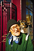 'An elderly man walks with his pet dog sitting on his shoulders, Portobello Road Market; London, England'
