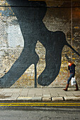 'A pedestrian walks by a brick wall with a woman's legs and feet in stilettos painted on the wall, Shoreditch; London, England'