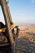 'Tourists in a hot air balloon taking pictures of the view below; Cappadocia, Turkey'