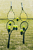'Tennis racquets and balls against a net on the grass; Tarifa, Cadiz, Andalusia, Spain'