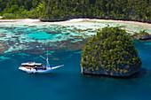 'A Bugis schooner, live-aboard dive vessel, at anchor in a limestone island lagoon; Uranie Island, Raja Ampat, West Papua, Indonesia'