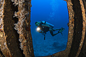 'A diver with a hand light outside of the wreck of the YO-257 off Waikiki Beach; Oahu, Hawaii, United States of America'