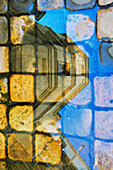 'Reflection in glass of a residential building and pavers on a walkway, Marais district; Paris, France'