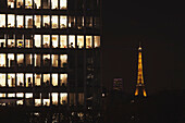 'Lights illuminated in the offices of an office building at nighttime with an illuminated Eiffel tower in the background; Paris, France'