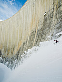 'Off piste skier skiing the walls of the Moiry Dam; Zinal, Switzerland'