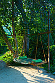 'A hammock hanging beside trees; Ulpotha, Embogama, Sri Lanka'