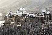 'Snow covered Banff Springs Hotel with snow covered trees and a Canadian flag; Banff, Alberta, Canada'