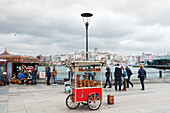 'Food cart and pedestrians at the waterfront; Istanbul, Turkey'