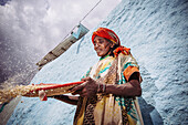 'A woman winnowing grain in the back streets; Harar, Ethiopia'