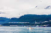 Coast Guard cutter returning to Valdez with misty clouds and mountains in the background, Valdez small boat harbor, Prince William Sound, Southcentral Alaska, USA.