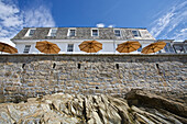 'Looking up a wall from the shore to a building and umbrellas on a patio on the seaside; St. Mawes, Cornwall, England'