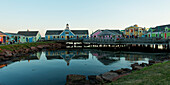 'Colourful buildings in Spinnakers Landing reflected in tranquil water; Summerside, Prince Edward Island, Canada'