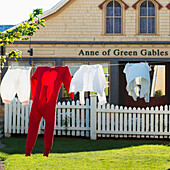 'Clothing hanging on the clothesline in front of a building with an Anne of Green Gables sign; Green Gables, Prince Edward Island, Canada'