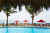 'Resort pool, umbrellas, palm trees and ocean view; Puerto Vallarta, Jalisco, Mexico'