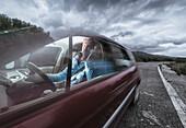 'A man talking on his phone while driving; Tarifa, Cadiz, Andalusia, Spain'