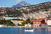 'Cliffs and buildings along the shoreline of Lake Garda with men fishing in the harbour; Torbole, Trentino, Italy'