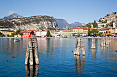 'Wooden pilings in the water in Lake Garda with buildings along the water's edge; Malcesine, Verona, Italy'